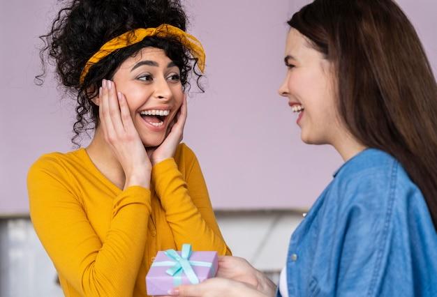 Mulheres sorridentes e felizes dando presentes umas às outras