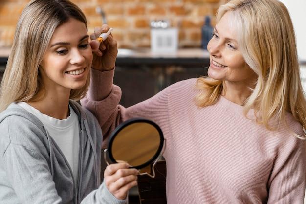Mulheres sorridentes em casa usando escova de maquiagem