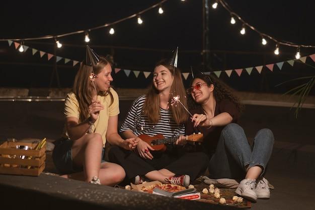 Mulheres sorridentes em cena completa com fogos de artifício