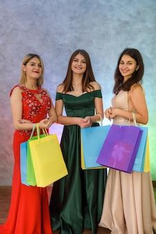 Mulheres sorridentes em vestidos elegantes, posando com sacos de presente no estúdio. presentes de natal
