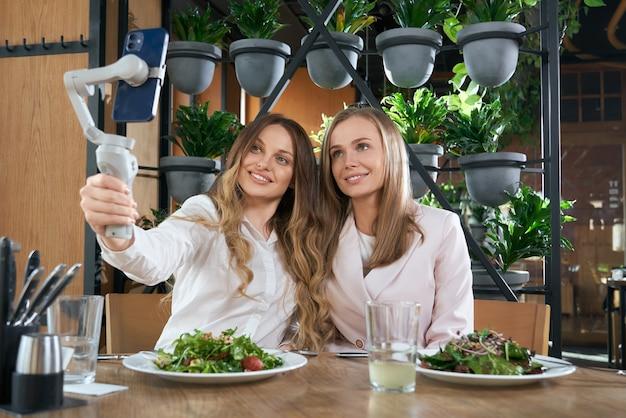 Mulheres sorridentes fazendo selfie com um telefone moderno em um café
