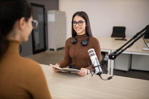 Mulheres sorridentes fazendo um programa de rádio