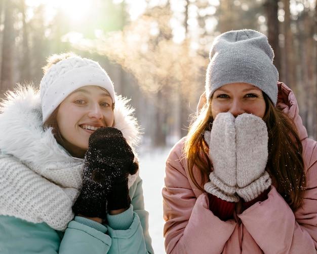 Mulheres sorridentes juntas ao ar livre no inverno