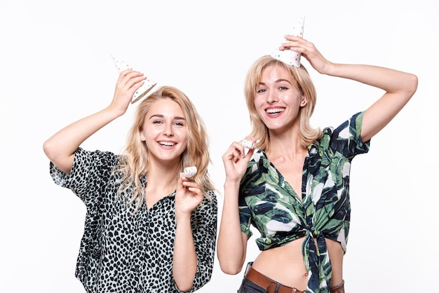 Mulheres sorridentes, levantando seus chapéus de festa