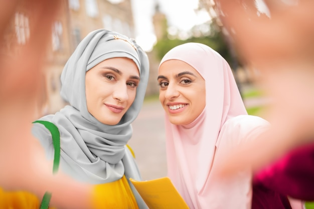 Mulheres sorridentes. mulheres muçulmanas de olhos escuros usando hijabs sorrindo enquanto fazem selfie