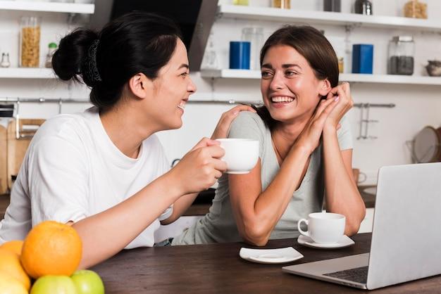 Mulheres sorridentes na cozinha com laptop e café