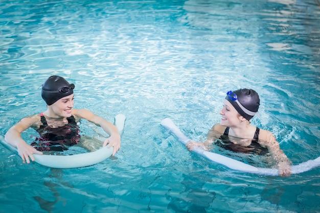 Mulheres sorridentes na piscina com rolos de espuma no centro de lazer