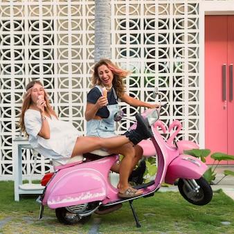 Mulheres sorridentes na scooter tomando sorvete