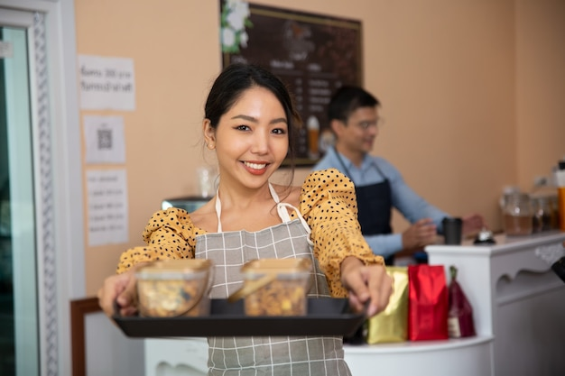 Mulheres sorridentes segurando biscoitos na cafeteria como proprietário de uma pequena empresa.