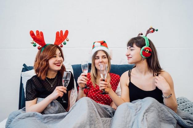 Mulheres sorridentes segurando copos de vinho e curtindo a festa do pijama
