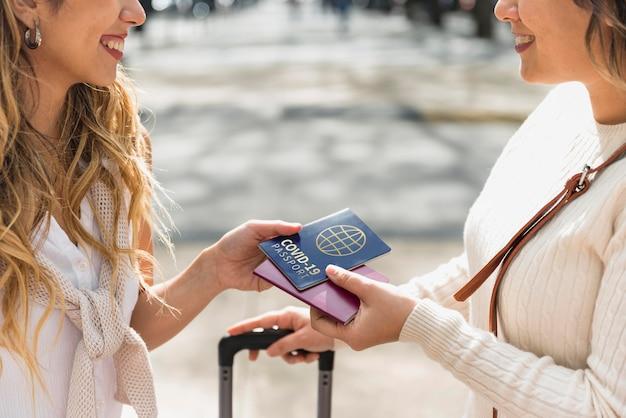 Mulheres sorridentes segurando passaportes de saúde