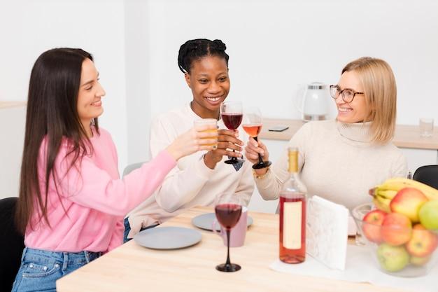 Mulheres sorridentes torcendo com um copo de vinho