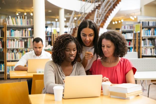 Mulheres sorridentes, trabalhando com o laptop na biblioteca pública