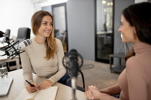 Mulheres sorridentes transmitindo juntas no rádio
