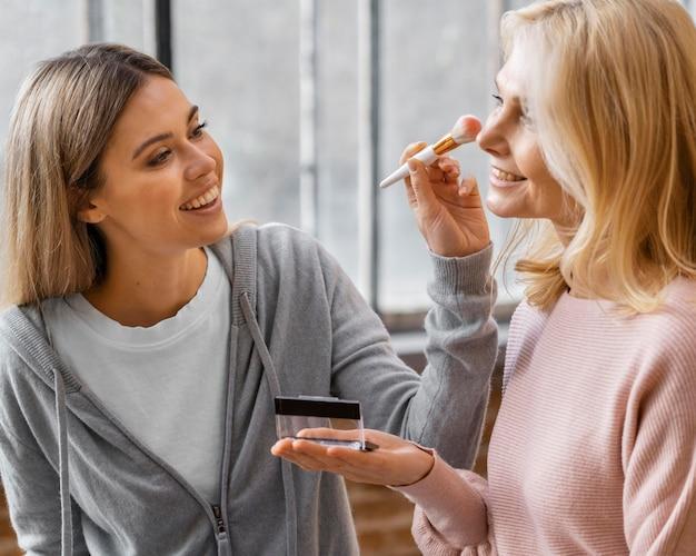 Mulheres sorridentes usando escova de maquiagem em casa