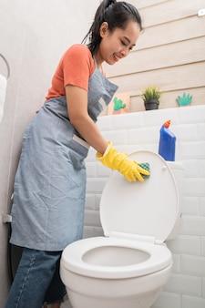 Mulheres sorridentes usando luvas limpando o banheiro com uma esponja no banheiro