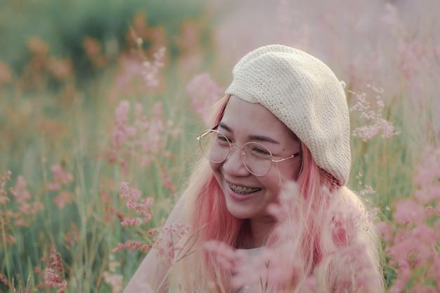 Mulheres sorrindo alegremente quando sentado no pasto. o rosto da jovem fica feliz quando ela sorri.