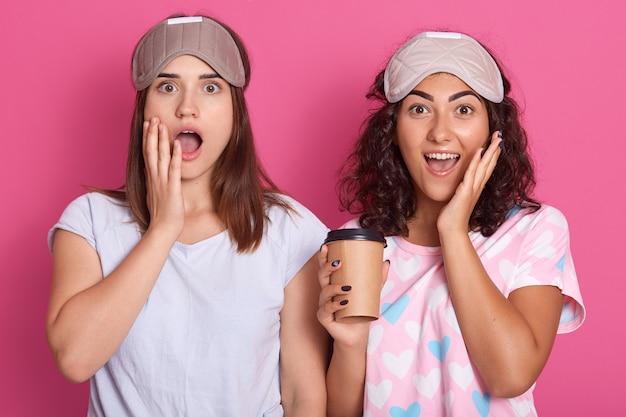Mulheres surpreendidas em pé com expressões faciais atônitas.