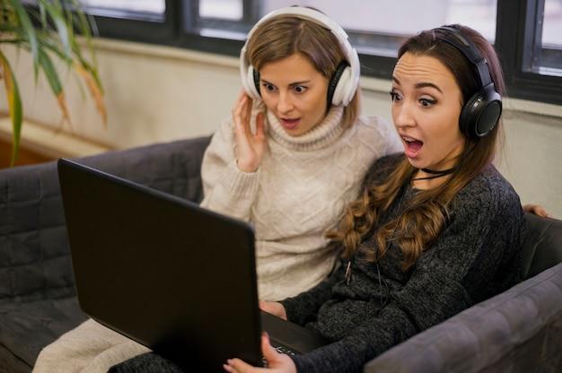 Mulheres surpreendidas usando fones de ouvido olhando para laptop