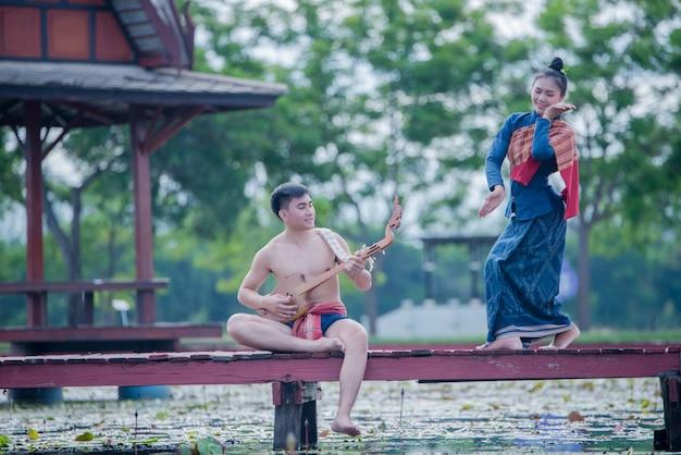 Mulheres tailandesas, e, homem, em, traje nacional, com, pino violão, (plucked, amarrado, instrumento)