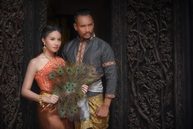 Mulheres tailandesas e homens tailandeses usando vestidos tradicionais tailandeses em belas casas tailandesas na província de ayutthaya.