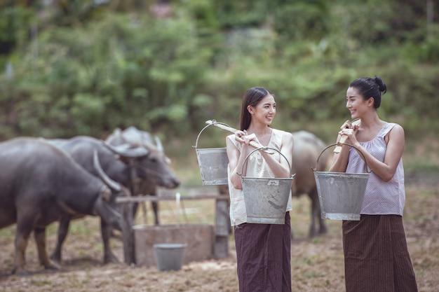 Mulheres tailandesas segurando baldes de água