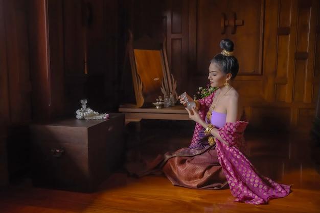 Mulheres tailandesas usam vestidos tradicionais tailandeses em belas casas tailandesas em ayutthaya.