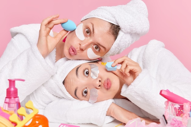 Mulheres têm surpresas expressões faciais manter os lábios dobrados, cabeças magras umas sobre as outras aplique patches de beleza com esponjas vestidas com roupões de banho brancos