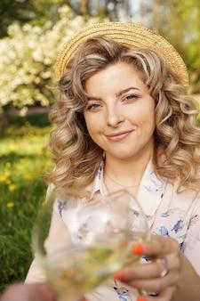 Mulheres tilintando de copos com vinho saboroso sobre fundo claro no dia de verão. loira feliz com cabelo encaracolado e um chapéu de palha