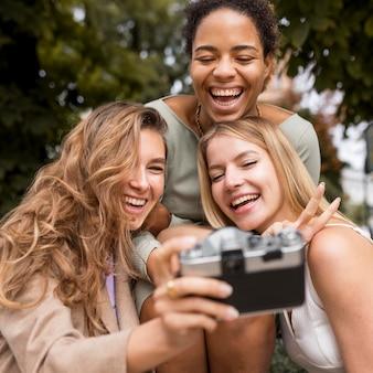 Mulheres tirando selfie com uma câmera vintage