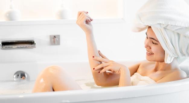 Mulheres tomando banho na banheira e jogando bolhas de sabão na sala de banho, ela se sente relaxada.