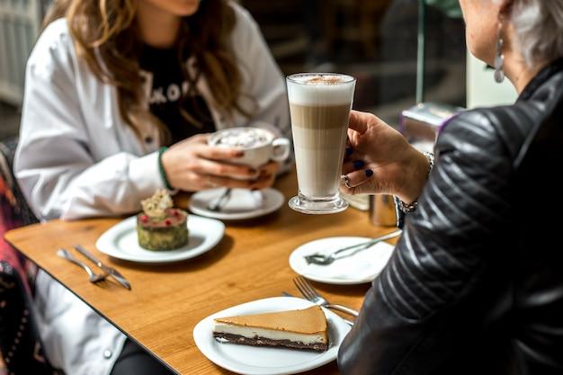 Mulheres tomando café com sobremesas bolo de queijo e pistache vista lateral