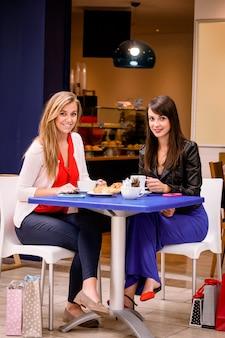 Mulheres tomando café e lanches em uma cafeteria