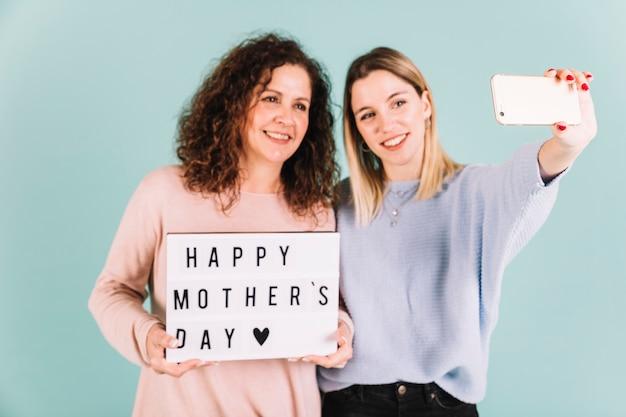 Mulheres tomando selfie com saudação de dia das mães
