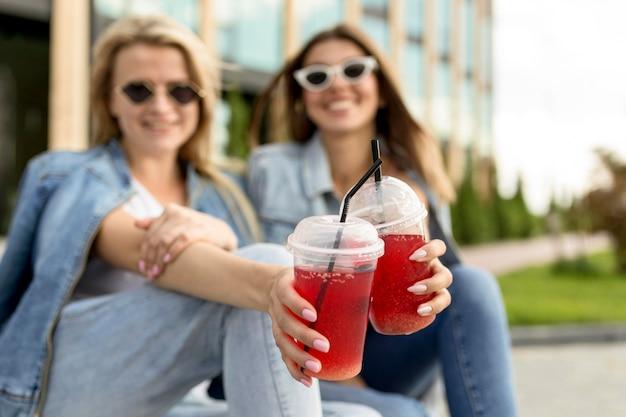 Mulheres torcendo com smoothies vermelhos