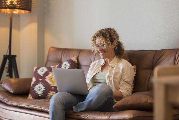Mulheres trabalhadoras inteligentes, estilo de vida, mulher feliz sentada no sofá, escrevendo ou fazendo videochamada