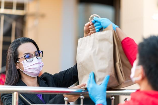 Mulheres trabalhadoras segurando sacola de papel com comida para viagem, entrega em domicílio, comida para viagem