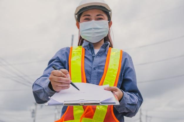 Mulheres trabalhadoras usam máscara facial segurando uma prancheta de pesquisa de trabalho