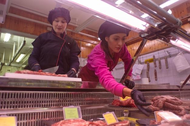 Mulheres trabalham no balcão da geladeira do açougue levando cortes de carne