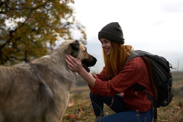 Mulheres turistas brincando com um cachorro ao ar livre viajam com alegria e amizade