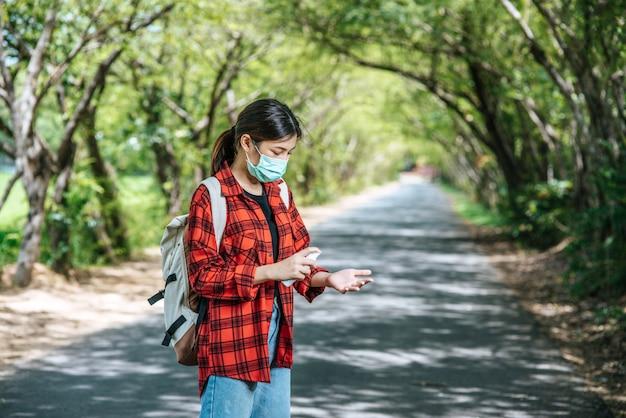 Mulheres turistas carregando uma mochila e em pé, injetando álcool nas mãos.