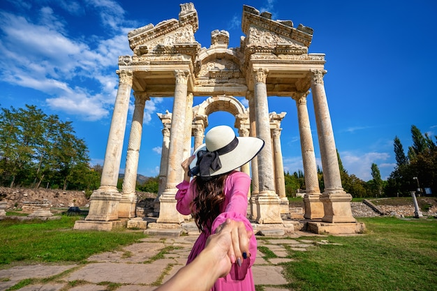 Mulheres turistas segurando a mão do homem e levando-o à antiga cidade de afrodisias, na turquia.