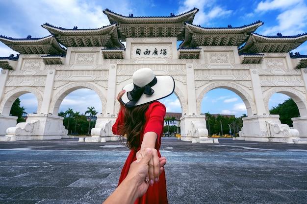 Mulheres turistas segurando a mão do homem e levando-o ao memorial de chiang kai shek em taipei, taiwan.