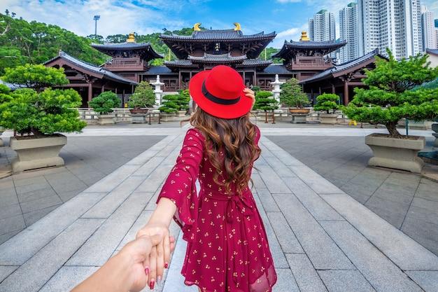 Mulheres turistas segurando a mão do homem e levando-o ao templo do convento de chi lin, em hong kong.