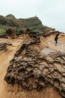 Mulheres turistas tirando uma foto do yehliu geopark, uma capa na costa norte de taiwan. uma paisagem de rochas de favo de mel e cogumelos corroídas pelo mar.