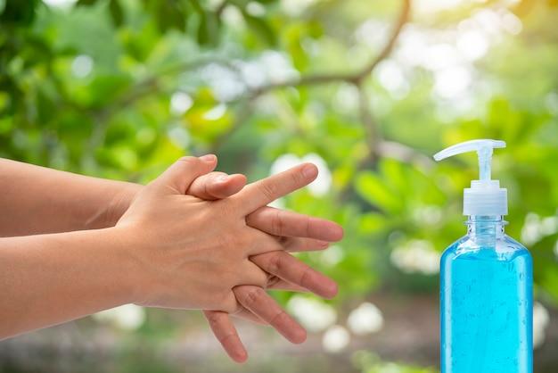 Mulheres usam álcool em gel para as mãos, lavando as mãos para proteção contra vírus infecciosos, bactérias, germes e covid-19.