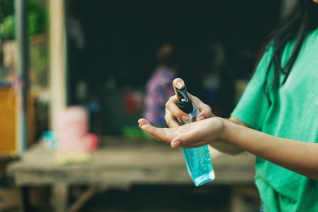 Mulheres usando álcool gel, desinfetante para as mãos, bomba distribuidora de mão