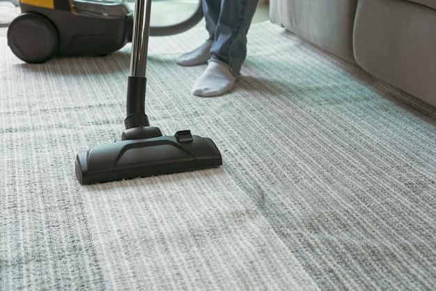 Mulheres usando aspirador de limpeza de carpete na sala de estar.