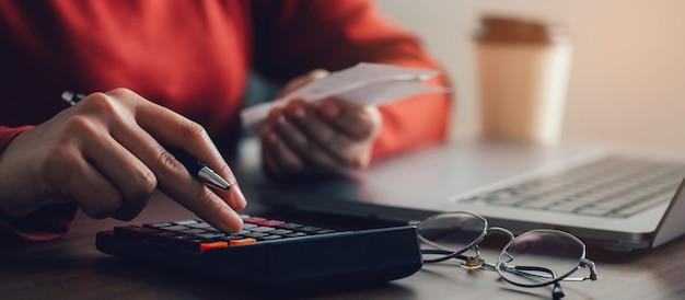 Mulheres usando calculadoras calculam contas domésticas em casa mulheres jovens cuidando da papelada