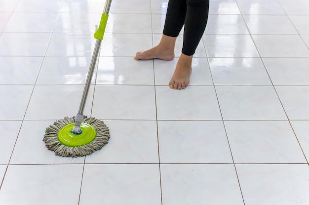 Mulheres usando esfregão, limpando o chão sujo da casa.